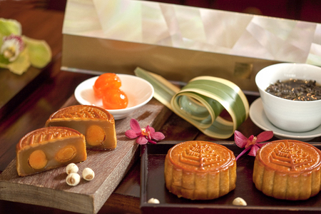 Four Tradditional Mooncakes with two cut up half to show egg yolk Stock Photo