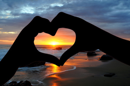Silhouette of hands in heart shape at sunset