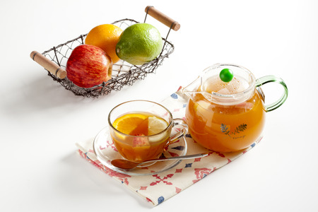 chamomilla: pot of orange tea and cup with fruit on white background