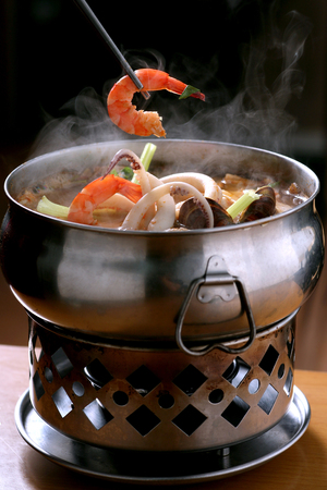 Traditional Chinese seafood hot pot with a shrimp held in a pair of chopsticks