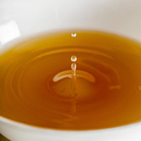 Wassertropfen fallen in eine Brühe, klare Suppe in einer weißen Tasse