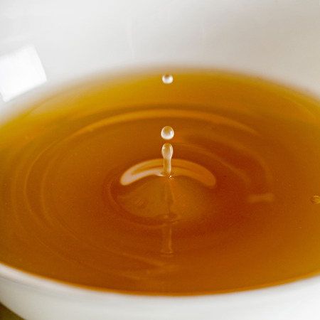 Water drop falling into a broth, clear soup in a white cup Stok Fotoğraf - 67678207