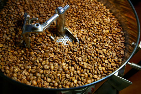 freshly roastd aromatic coffee beans over a modern machine used for roasting beans Stock Photo