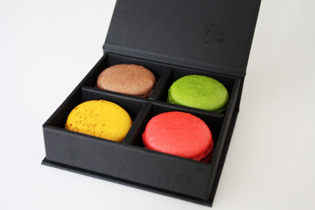 Colorful macarons in black box on white background