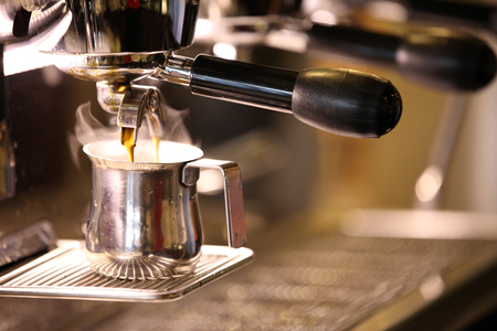 Coffee espresso. Espresso machine making coffee golden espresso flowing. Stock Photo