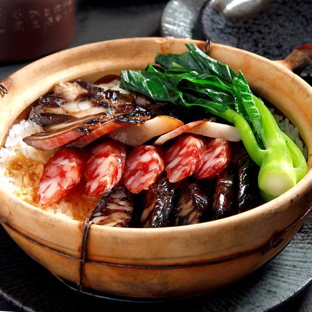 Comida cantonesa, salchicha china y pollo con arroz en la olla de barro Foto de archivo - 70286863
