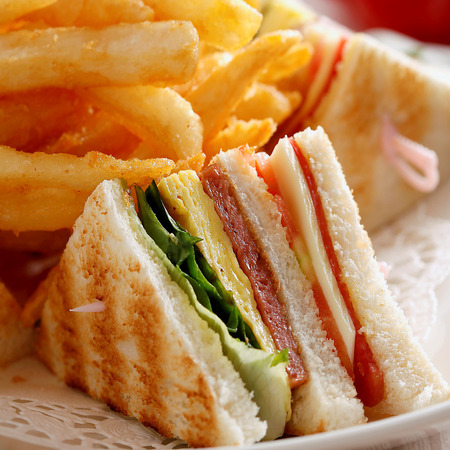 encurtidos: Close up of club sandwich with french fries