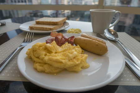 angled view: Breakfast with scambled eggs, sausage and bacon Stock Photo