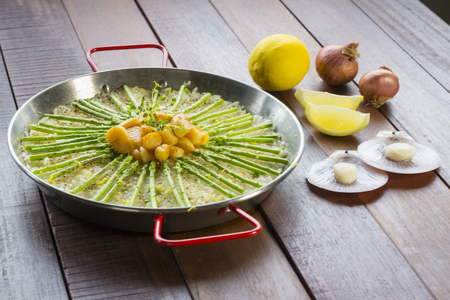 Paella with scollops and asparagus in traditional pan. Stock Photo
