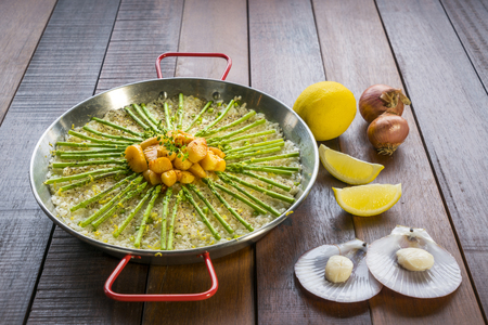 coquille: Paella with scollops and asparagus in traditional pan. Stock Photo