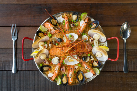 Gourmet seafood Valencia paella with fresh langoustine, clams, mussels and squid on savory saffron rice with prawn, scollops, mussels and lime slices, close up view
