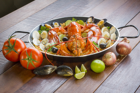 conceptional: Gourmet seafood Valencia paella with fresh langoustine, clams, mussels and squid on savory saffron rice with peas and lemon slices, close up view Stock Photo