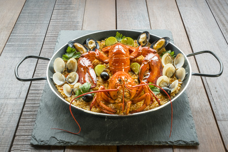 Gourmet seafood Valencia paella with fresh langoustine, clams, mussels and squid on savory saffron rice with peas and lemon slices, close up view Stock Photo