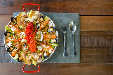 Gourmet seafood Valencia paella with fresh langoustine, clams, mussels and squid on savory saffron rice with peas and lemon slices, above view Stock Photo