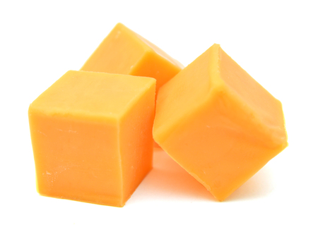 pieces of sharp cheddar cheese on a white background.