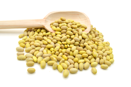 Raw canary beans (peruano beans, yellow beans) and wood spoon on white background