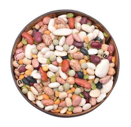 A mixture of legumes in an earthenware bowl, white background.