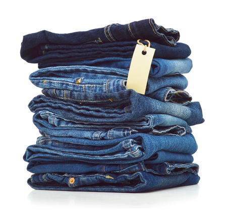 Stack of blue jeans and blank card on white background