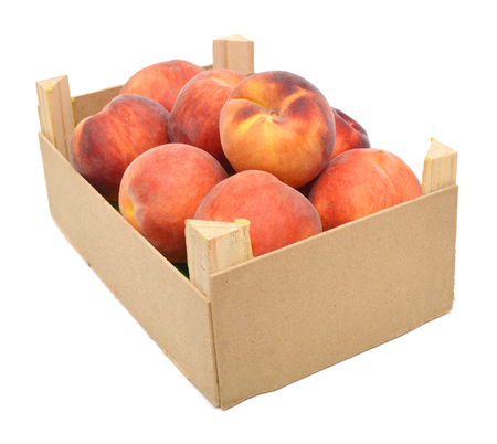 Many peaches in wooden crate on white Фото со стока