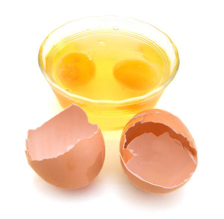 brown egg and glass bowl on white background Stock Photo