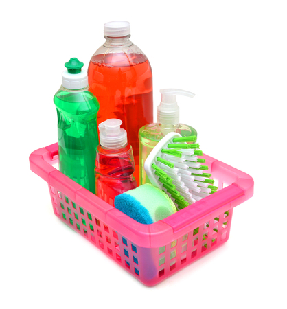 Plastic bottles of cleaning products, sponges and brush in basket on white background