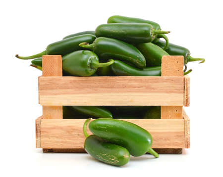 bunch of fresh green chili peppers in wooden crate on a white background
