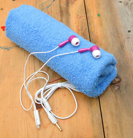 Pink and white earphones nd towel on wooden board