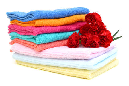 Stack of colorfull towels and carnation flower isolated on white