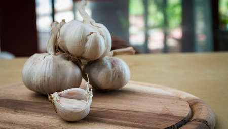 lobes: garlic lobes, seasoning herb and spicy, had been placed on the brown wooden plate.