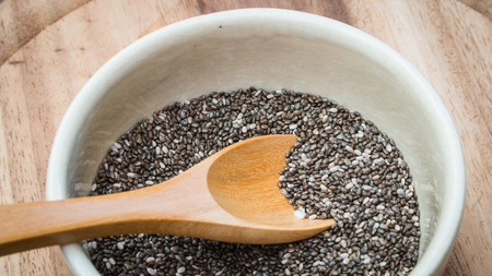 chia seed: Closeup wooden spoon on Chia seed bowl.