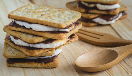 Smores placed on wooden table beside with wooden fork and spoon Stock Photo