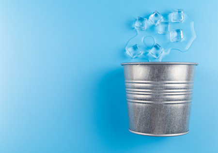 melting ice and metal bucket on blue background