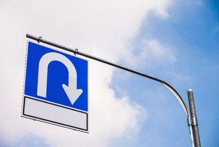 U-Turn sign with blue sky background, road sign symbol Stock Photo