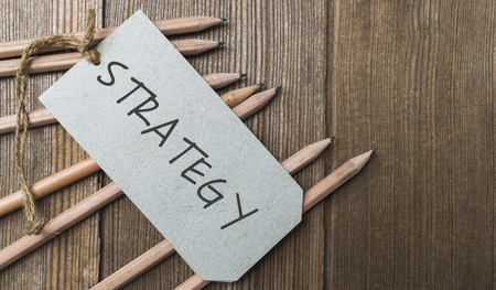 Word Strategy in brown paper tag on wooden table with many pencils, business concept Stock Photo