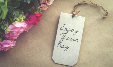 Enjoy your day card on brown paper with artificial roses