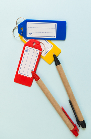 colorful plastic tags and pencils on blue background, view from above