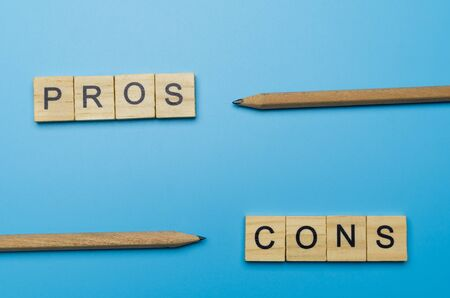 """Pros and Cons"" word in the wooden block on blue background pointed by pencil"