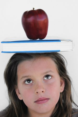 young school girl looking up at book and apple