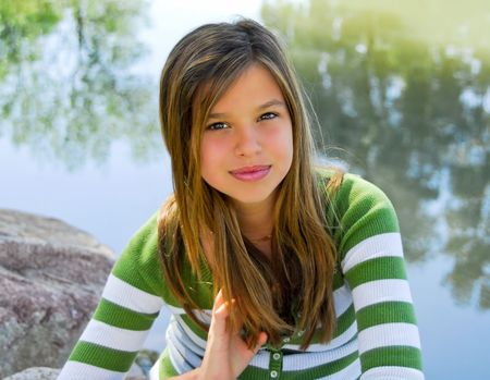 young pretty girl outdoors by a pond