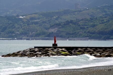 Breakwater on the beach and the waves
