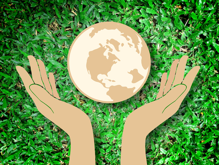 paper background: hand holding the world save the world symbol on Grass background
