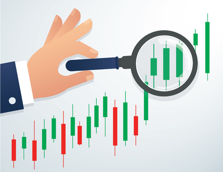 Hand holding the magnifying glass and candlestick chart stock market.