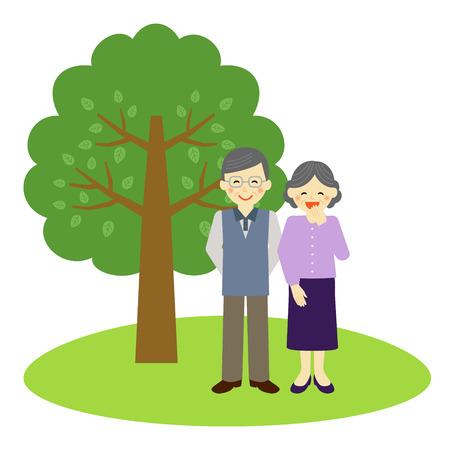 vecchiaia: Felice coppia senior in piedi vicino all'albero