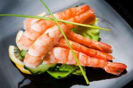 Five shrimps served with salad, sliced lemon and cucumber.Close up photo