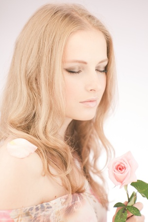 Soft portrait of beautiful girl with a pink rose Stock Photo - 11251201