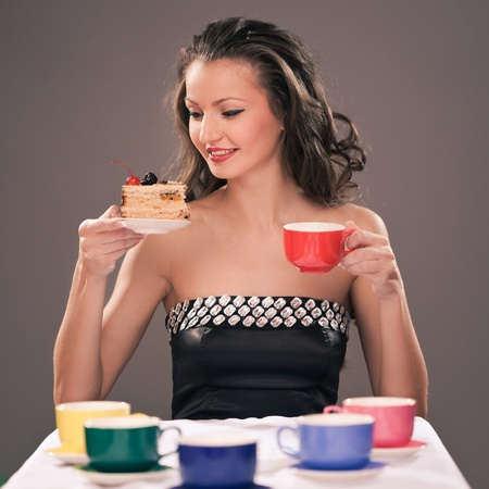 Pretty young girl sitting with cake and cups of different color photo