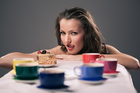 Pretty young girl with cake and colorful cups photo