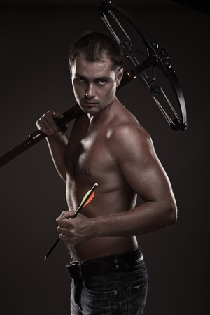 crossbow: Attractive young man with crossbow over black background
