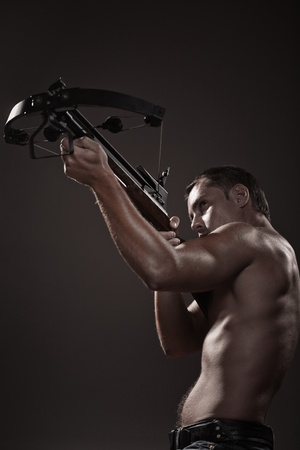 Attractive young man with crossbow over black background photo
