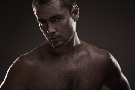Attractive young man covered with water drops